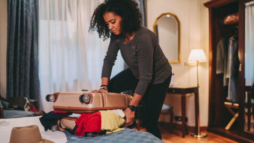 Mixed race woman unable to close suitcase before leaving the hotel room.