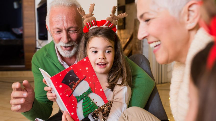 Joyful older couple reading Christmas card to their granddaughters.