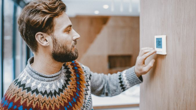Man in sweater feeling cold adjusting room temperature with electronic thermostat at home.