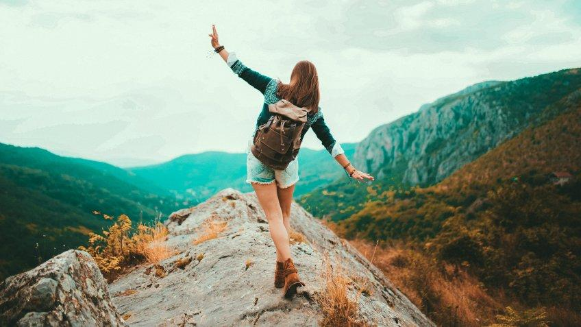 Young Hippie girl taking a walk on top of a mountain and enjoying the day.