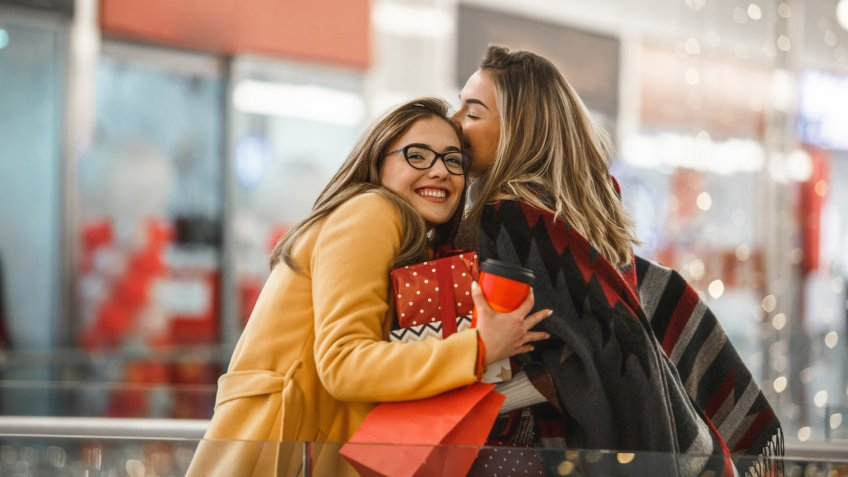 Beautiful young women are hugging and sharing presents after shopping.