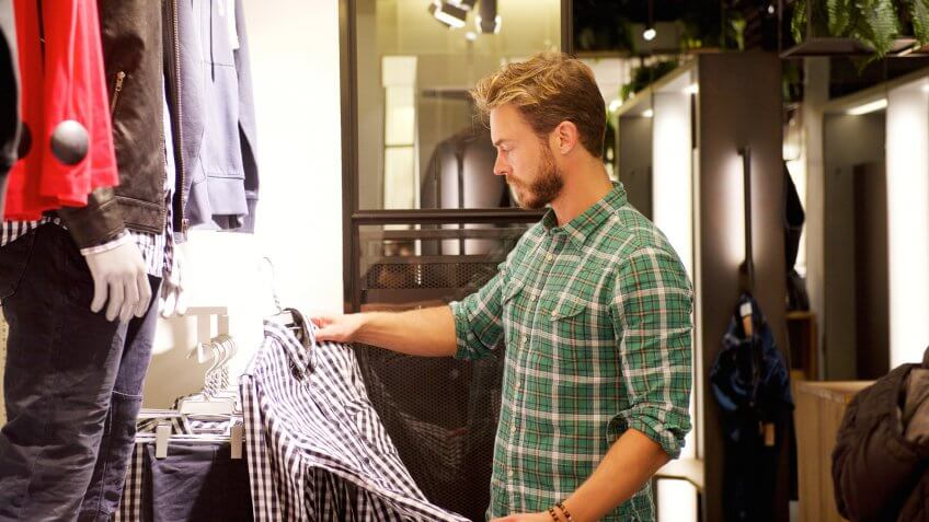 Portrait of a male shopper looking at clothes in store.