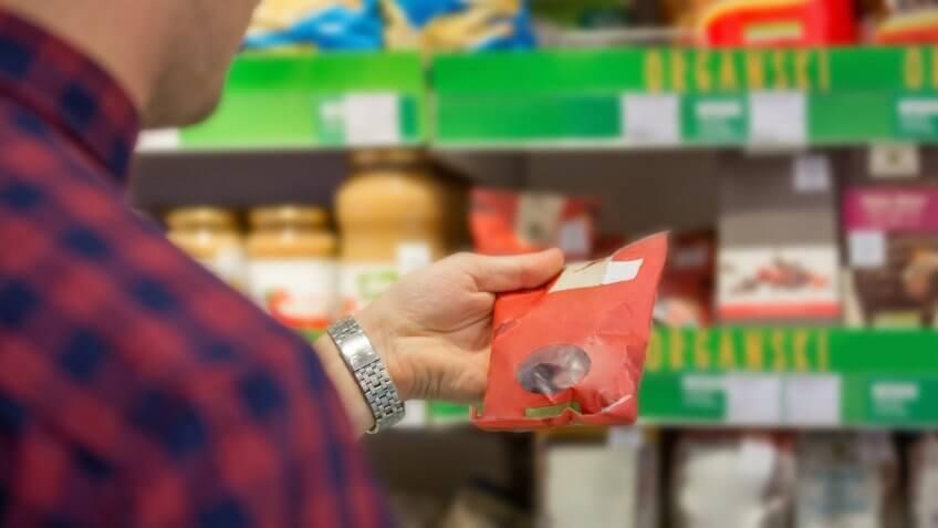Man choosing snacks in supermarket.