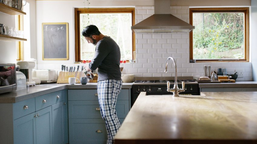 Shot of a man making two cups of coffee in the kitchen at home.