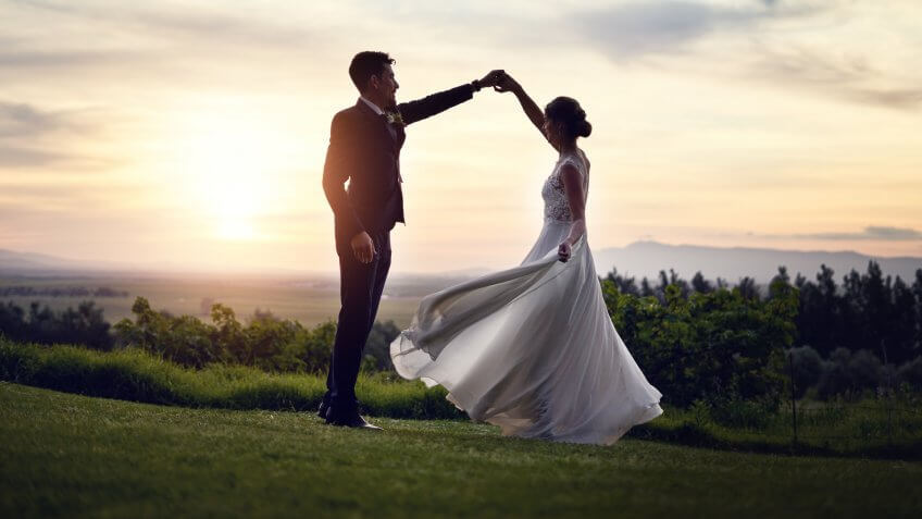 married couple dancing at sunset in field