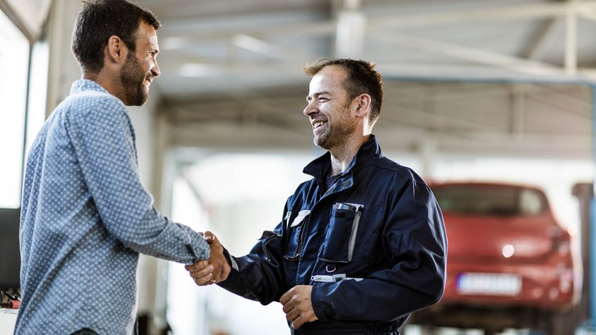 Happy mechanic came to an agreement with his customer in auto repair shop.