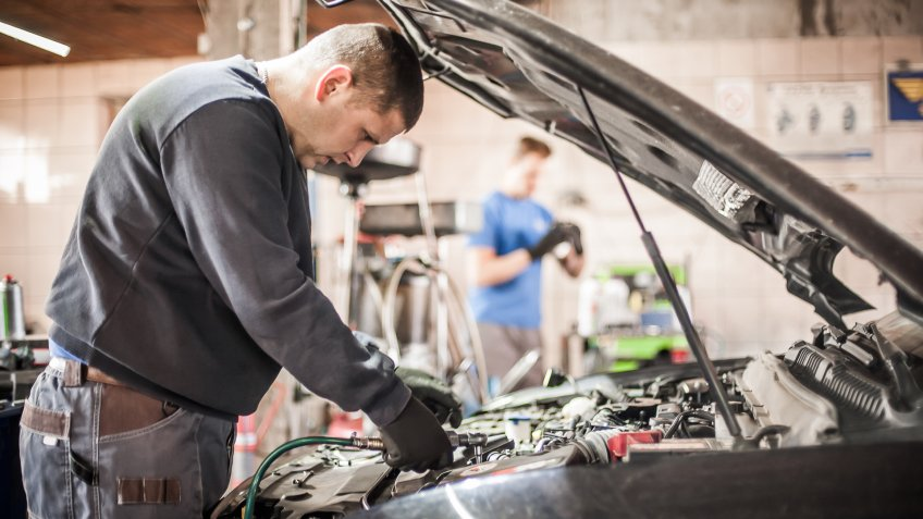 Two car master auto mechanic repairers service technician checks and repairs the engine condition under the hood of the vehicle service shop.