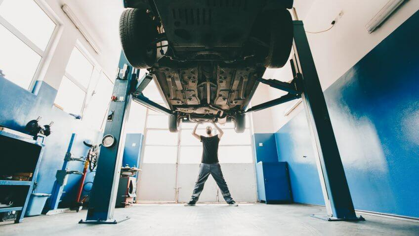 Young mechanic prepairing the car for inspection,distant view,bright light.