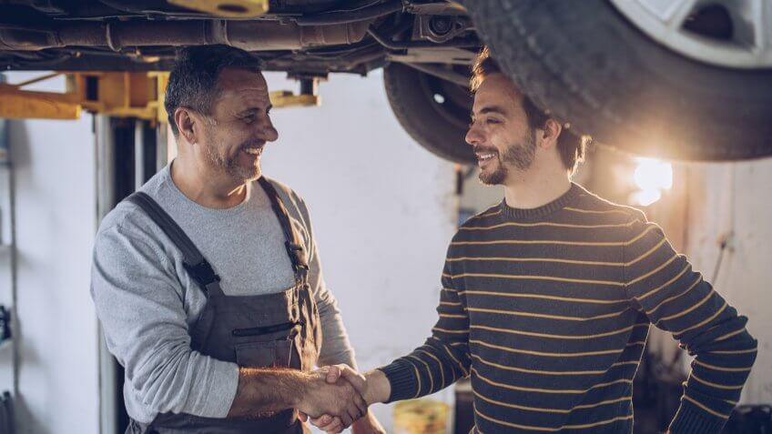 Mature adult auto mechanic, standing under the car, shaking hands with his customer, job is done.