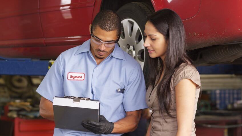 Mechanic in auto repair shop works with customer.