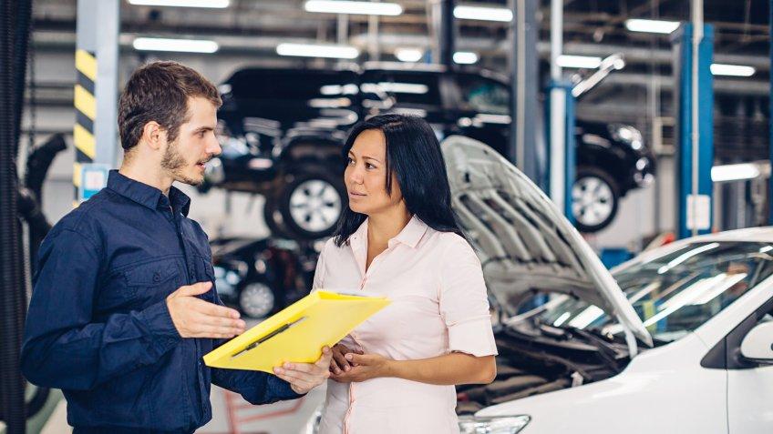mechanic speaking with female customer in garage