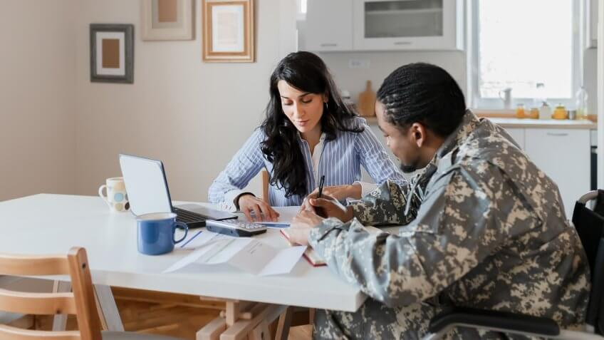 Disabled African American Male Soldier in a Wheelchair in Military Uniform With Female Financial Advisor Consulting About Financial Paperwork, Doing Household Accounting at Home.