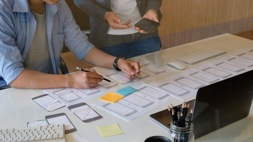 Website designer planning application development draft template layout framework and coding program on paper and computer.