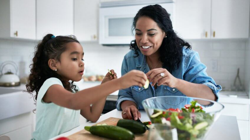 Mother and daughter preparing meal at home.