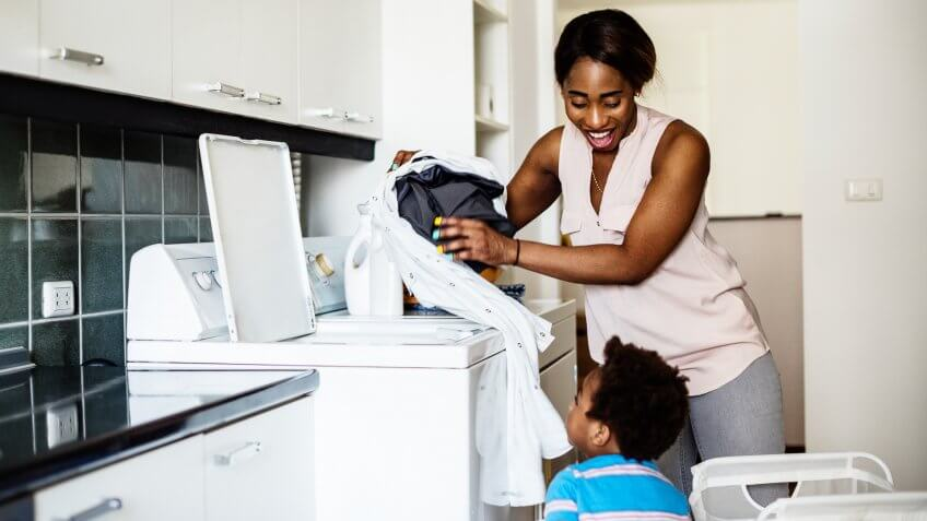 African descent kid helping mom doing the laundry.