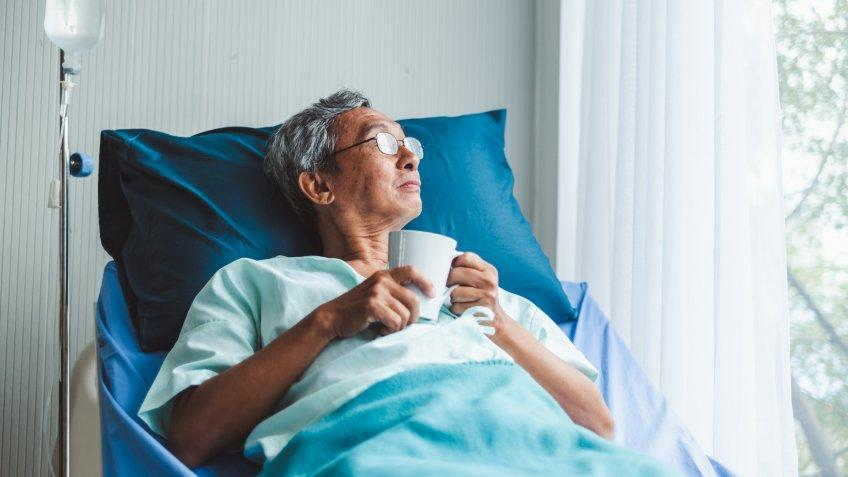 Lonely old asian patient on patient bed in hospital.