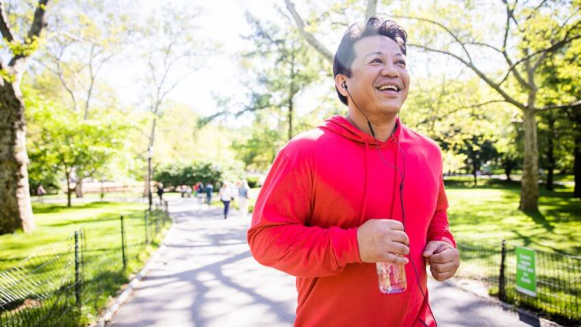 A mature hispanic man working out in central park in New York City.