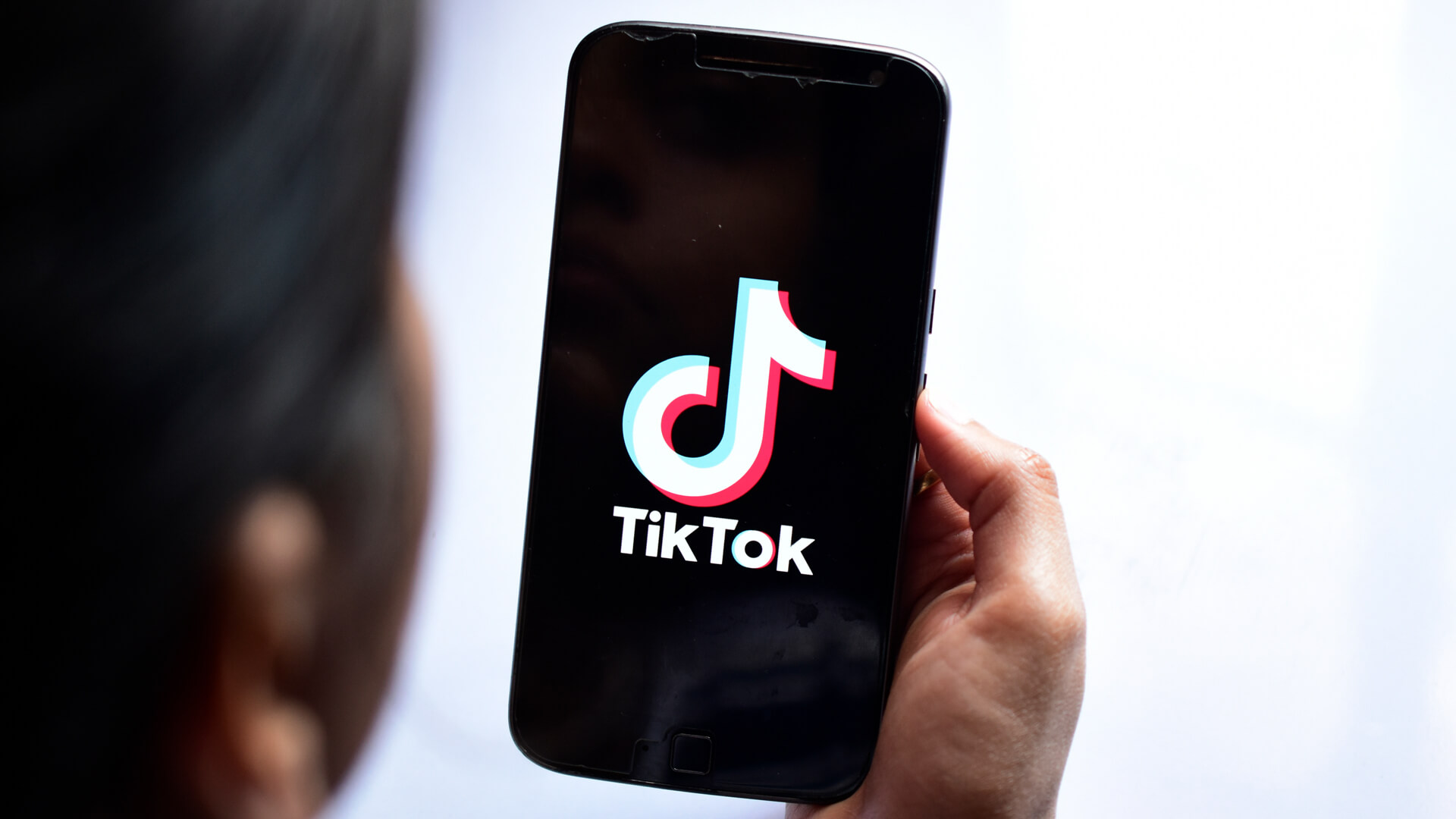 New Delhi, India - April 23, 2019: Woman holding motorola phone with ban streaming service media and video TikTok application on the screen.