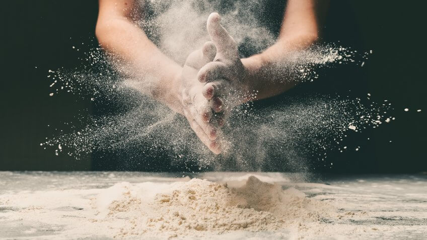 Clap hands of baker with flour in restaurant kitchen.