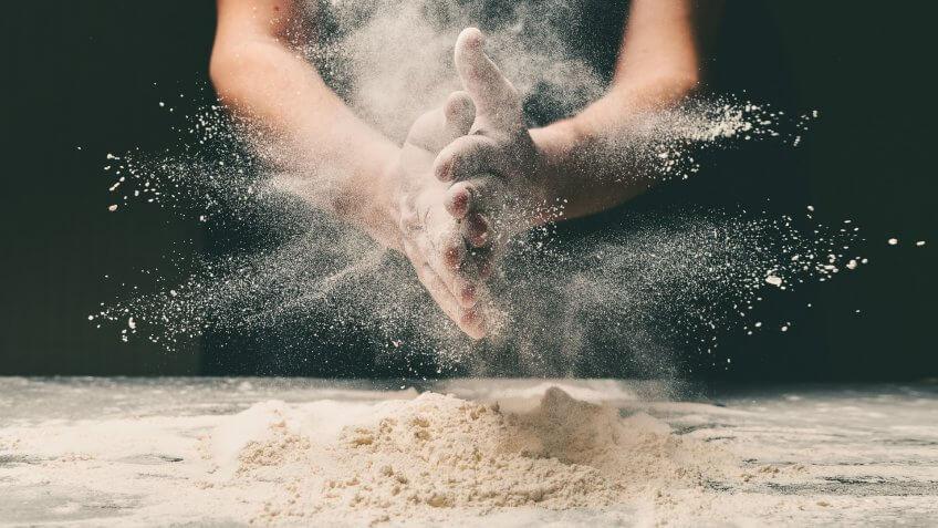Clap hands of baker with flour in restaurant kitchen.