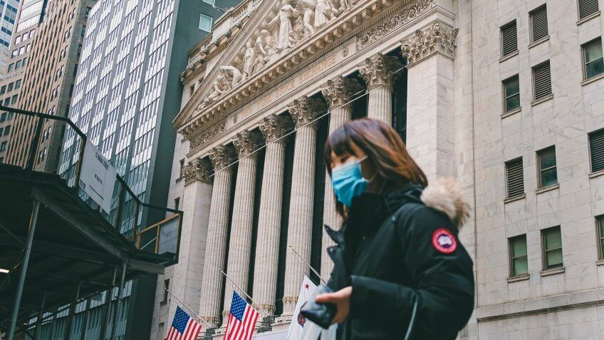 A person wearing a face mask walks past the New York Stock Exchange in New York, New York, USA, 27 January 2020.