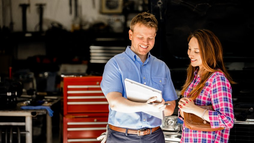 Happy customer!  A smiling Latin descent woman discusses automobile repair invoice with an auto mechanic in a repair shop.