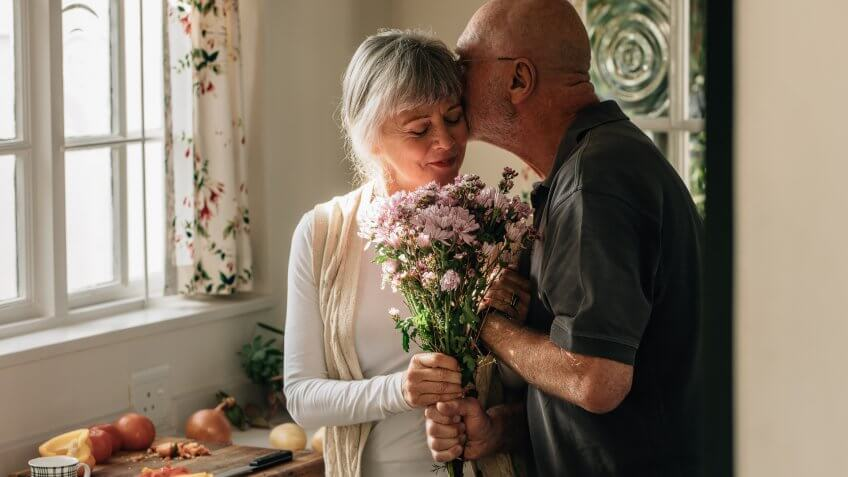 Senior couple standing in kitchen holding a bunch of flowers.