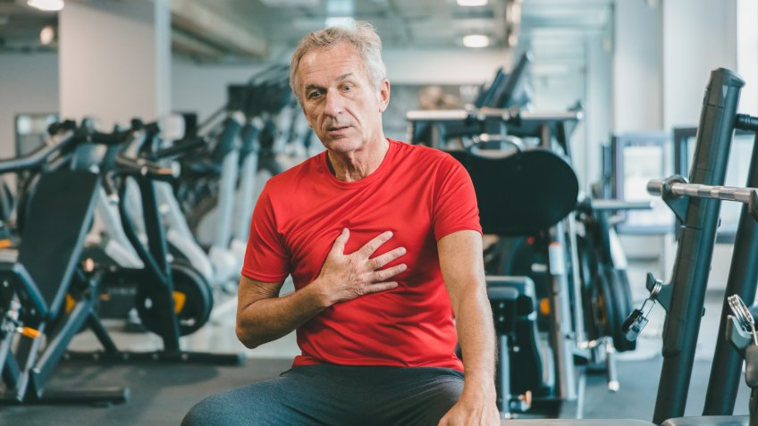 Shot of a elderly man feeling chest pain at gym.
