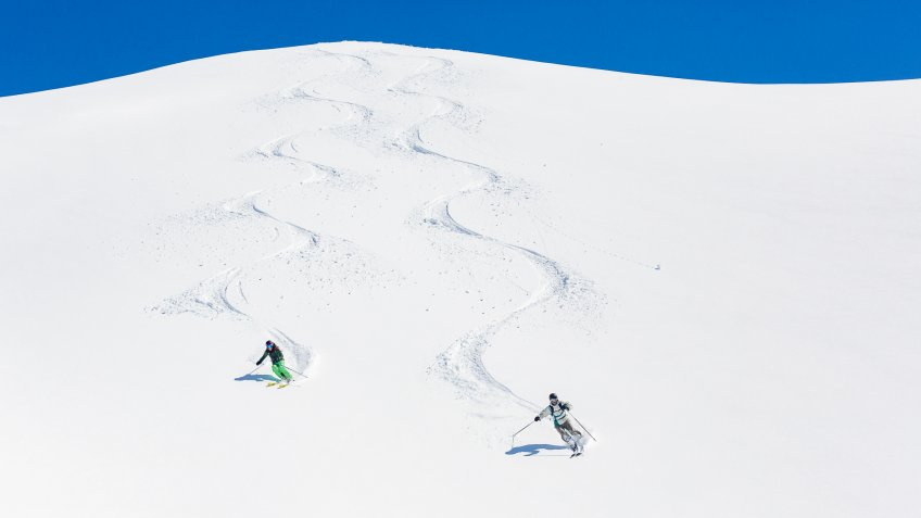 Man and woman skiing down mountain leaving tracks behind.