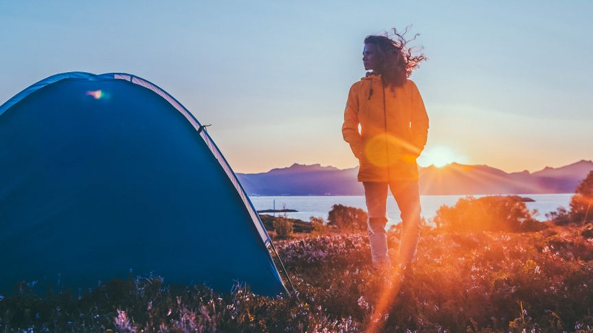 solo woman camping alone at sunset
