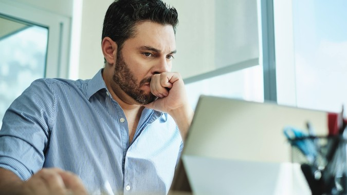 Angry Hispanic businessman working with laptop computer in office, losing patience.