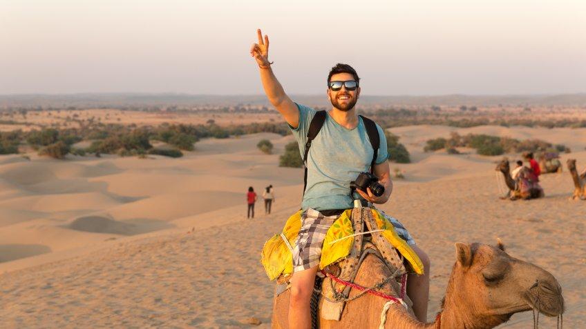 Tourist riding camel in Desert.
