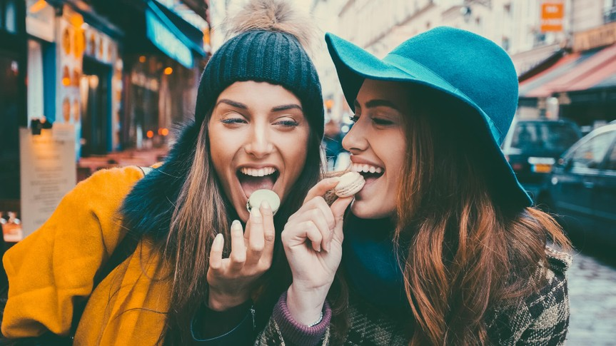Two women at journey in France tasting macaroon cookies.