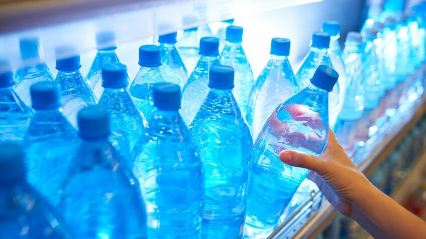 Female hand taking bottle of water from shelf.