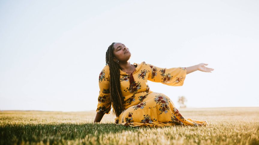 A beautiful young adult African woman enjoys the beauty of the summer , her eyes closed in prayer, worship, or meditation.