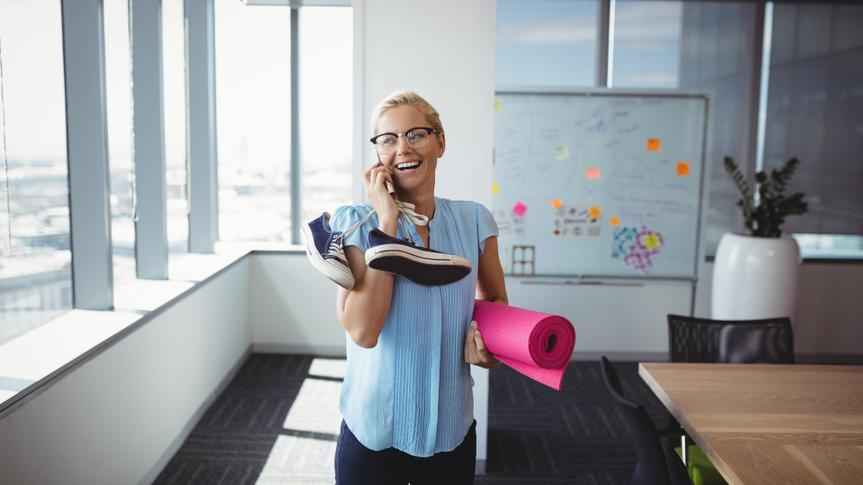 Smiling executive talking on mobile phone while holding exercise mat and shoes in office.