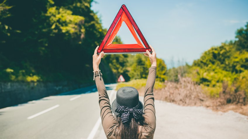 Young caucasian woman standing on a road and holding road triangle asking for help.