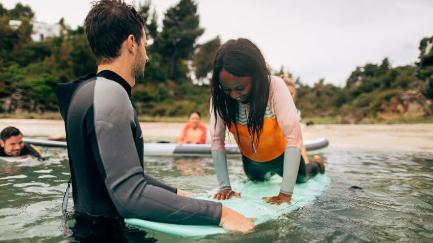 Young woman and her instructor having surfing class in the sea.