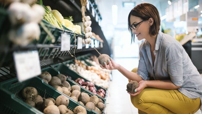 Attractive brunette woman choosing lettuce to buy in a supermarket.