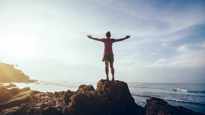 Freedom woman outstretched arms on sunrise seaside rock cliff edge.