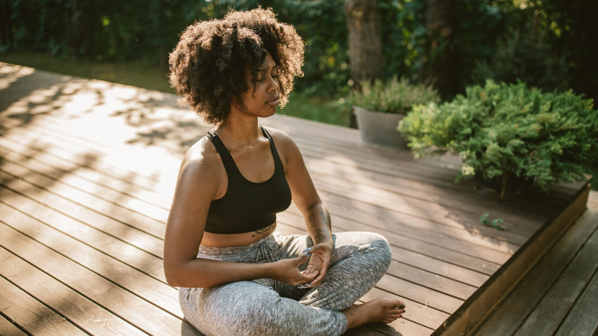 Young woman practicing yoga outdoors on porch, she enjoy in summer sun and meditation.