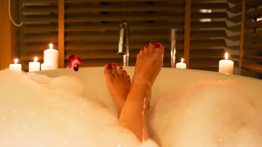 Back view of the feet of the young woman in bath with foam and candles.