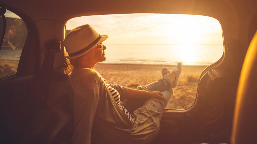 Young woman sitting in the trunk of a car on a beach in sunset.