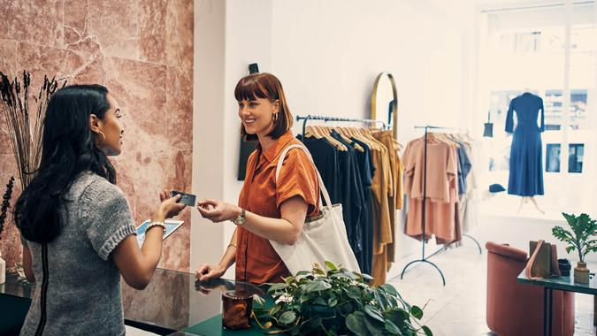Shot of a customer paying with a credit card in a clothing store.