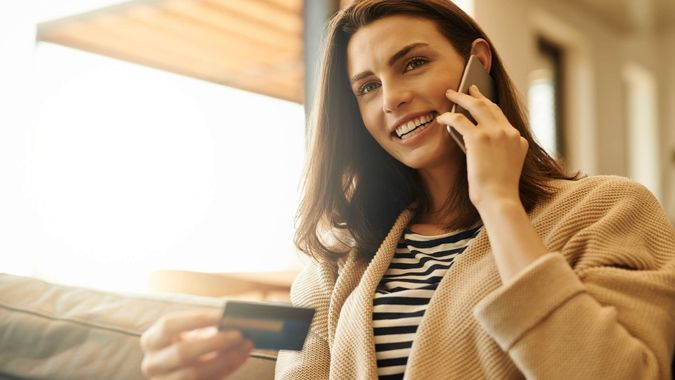 Shot of a beautiful young woman using a cellphone and credit card at home.