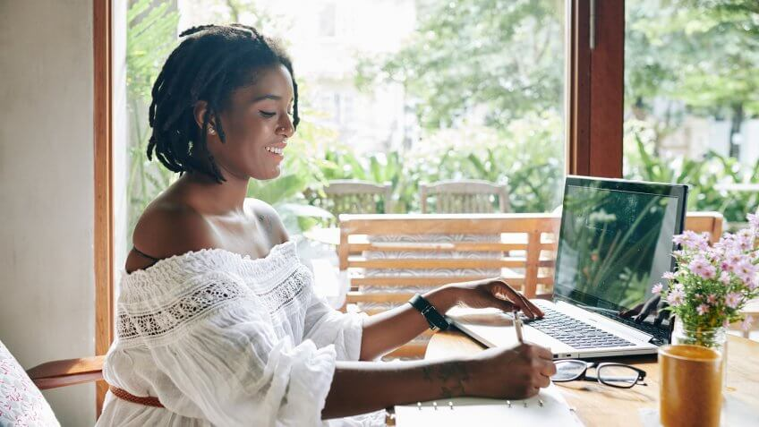African happy woman sitting at the table in front of laptop and writing in document she working at home.