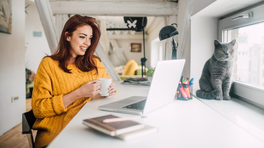 Smiling young redhead holding a cup of coffee while working on her laptop in her home office with a cat sitting in a window.