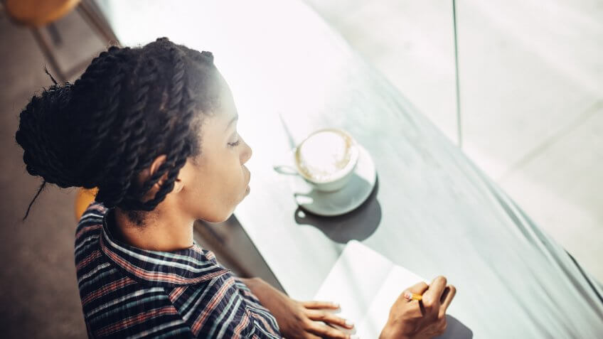 A beautiful young African American woman sits at the window counter of a coffee shop, enjoying a latte while writing ideas down in a small notepad journal or diary.