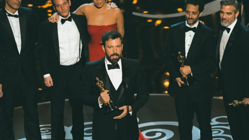 """Director/producer Ben Affleck, center, accepts the award for best picture for """"Argo,"""" as the cast and crew look on during the Oscars at the Dolby Theatre, in Los Angeles85th Academy Awards - Show, Los Angeles, USA - 24 Feb 2013."""