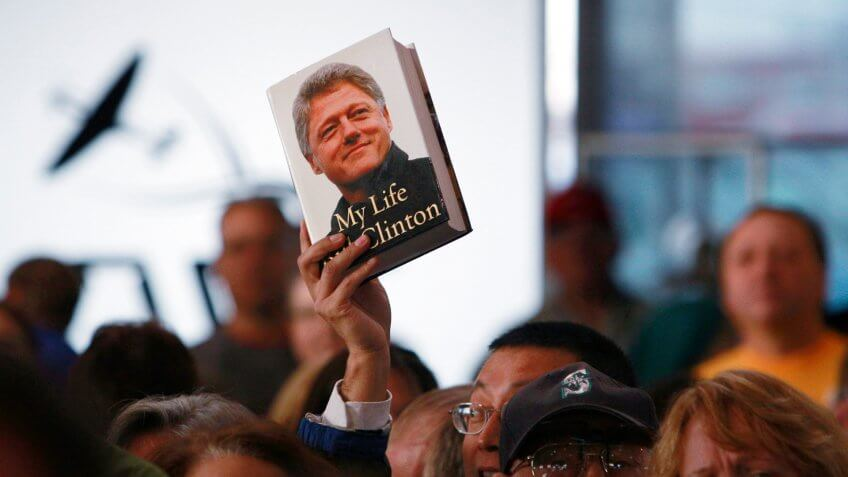 A book by former President Bill Clinton is held up as he speaks at a campaign event for Sen.